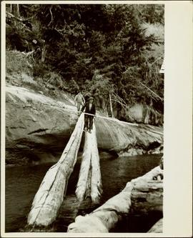 Two men walking across a large log over water at Knight Inlet