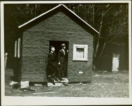 A Priest and a man standing in the doorway of a small house under construction