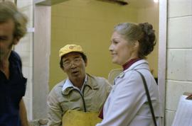 Iona Campagnolo standing with a male worker while on tour of a fish cannery