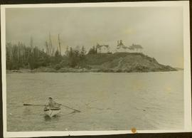 Woman wearing Cowichan sweater rowing a boat away from a lighthouse