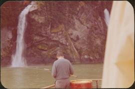 J. J. Claxton fishing by a waterfall on board the Columbia