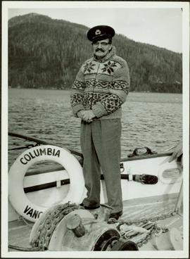J. J. Claxton wearing Cowichan sweater standing on the deck of the M.S. Columbia