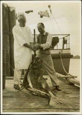 Two men displaying their large peughed hailbut on the dock