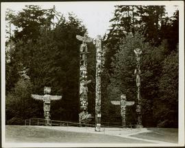 Five totem poles of various sizes standing within a fenced enclosure