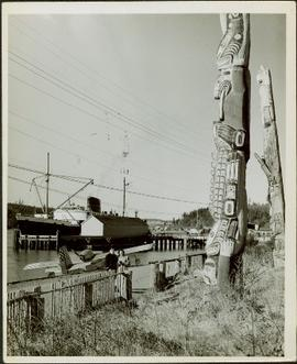 A man in uniform and a woman pose for a photo in front of totem poles