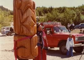 Woman in button blanket standing beside totem pole at opening of Haisla Recreation Centre in Kita...