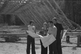 Iona Campagnolo and construction workers looking at plans at construction site