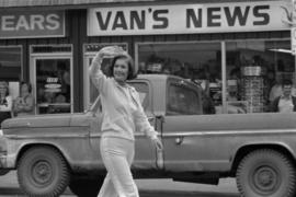 Iona Campagnolo waving to crowd in front of Van's News store while walking in parade in Smit...