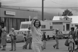 Iona Campagnolo waving to crowd in front of Smithers Bridal Store while walking in parade