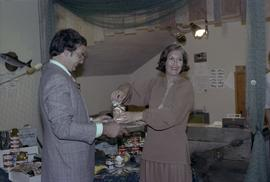 Iona Campagnolo opening can of salmon held by man at the opening of the Prince Rupert Fishing Exh...