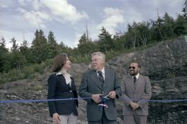 Iona Campagnolo, man, and Joe Scott with scissors cutting ribbon at opening ceremony for Scott Ro...