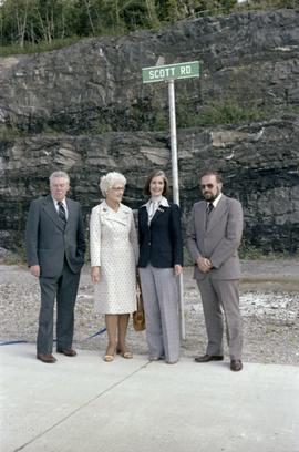 Iona Campagnolo, Joe Scott, and others posing by Scott Road sign at opening ceremony