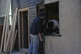 Assistant to Iona Campagnolo and man work on a window frame in a house under construction