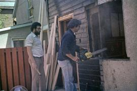 Assistant to Iona Campagnolo and man with chainsaw work on a window frame in a house under constr...