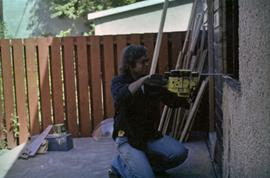 Man with chainsaw cutting window frame in house under construction