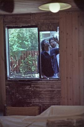 Assistant to Iona Campagnolo and man install a window in a house under construction