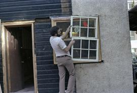 Assistant to Iona Campagnolo holding window in a house under construction