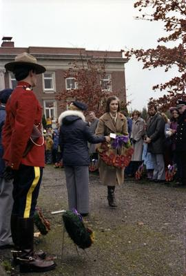Iona Campagnolo walking with wreath in front of Prince Rupert courthouse at Remembrance Day ceremony