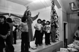 Iona Campagnolo on stage with Glen Vowell First Nations children at potluck following key present...
