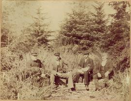 Four Men Seated on Log in Forest