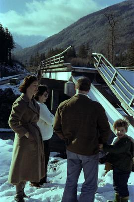 Iona Campagnolo with a family at damaged road and bridge from washout on Highway 16