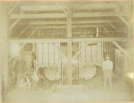 Men and Boy standing next to dear kill at cannery retorts