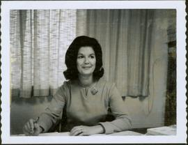 Close-up of Iona Campagnolo sitting at table in front of curtained window, holding a pen, 1964