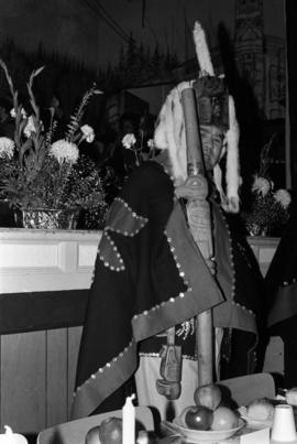 Dempsey Collinson wearing button blanket and head dress and holding a carved staff in Skidegate