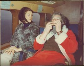 Iona Campagnolo in helicopter with unidentified man dressed as Santa on a CHTK radio Christmas Lighthouse tour, Prince Rupert, December 1970