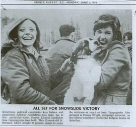 Iona Campagnolo being kissed by a twelve week St. Bernard puppy while visiting the Kispiox Rodeo with campaign assistant Teresa Wright