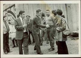 Jean Chretien shaking Iona Campagnolo's hand in front of a Tsimshian longhouse while several unidentified people look on