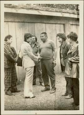 Iona Campagnolo shaking hands with an unidentified First Nations man in front of a longhouse while several others look on