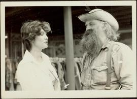 Iona Campagnolo talking to an unidentified bearded man wearing cowboy hat, suspenders, and denim work shirt