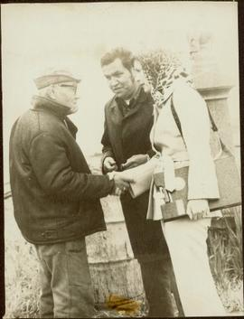 Iona Campagnolo holding a clipboard and shaking hands with an unidentified man while another man ...