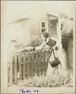 Iona Campagnolo reaching over a fence to shake hands with W. Neil Sterritt in his front yard in Massett, BC