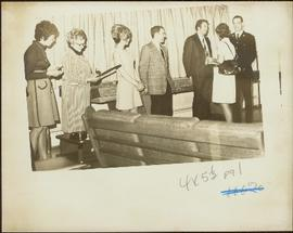 Three unidentified women and three unidentified men stand in a line in a curtained room as Iona Campagnolo talks to one of the men
