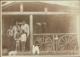 Iona Campagnolo stands on the porch of a log cabin with her arms around unknown family