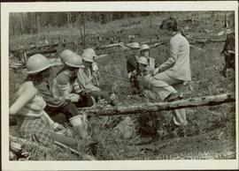 Iona Campagnolo talks to group of eight unidentified women in hardhats inside a clearcut