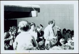 Iona Campagnolo standing behind Pierre Trudeau while he speaks to a crowd of people