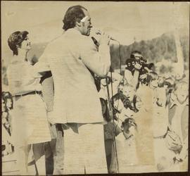 Pierre Trudeau speaks to crowd, arm around unidentified man, and Iona Campagnolo behind him