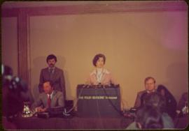 "M.P. Iona Campagnolo speaking at podium labeled ""The Four Seasons Vancouver"" with three unidentified men sitting at her sides"