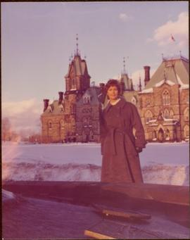 M.P. Iona Campagnolo posing in front of Parliament buildings in Ottawa, winter 1976