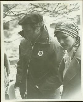 Close View of Prime Minister Pierre Trudeau wearing a beret and Mustang lifejacket, walking outside beside M.P. Iona Campagnolo in headscarf and wool jacket, Kivsta, Haida Gwaii, BC