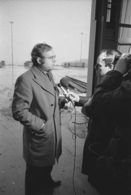Otto Lang talking to reporter with microphone during visit to Prince Rupert Fairview Cargo Terminal