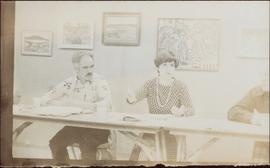 Iona Campagnolo speaking at long table as two men listen, 1976