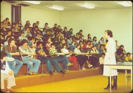 Minister Iona Campagnolo speaking to a lecture hall of youths at Granisle School, Granisle, BC