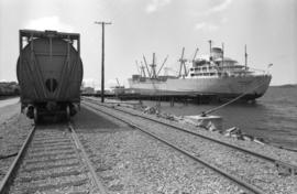 "CN grain car on railroad tracks and docked ship ""Aegean Sea"" in Prince Rupert"