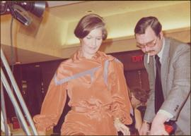 Minister Iona Campagnolo looks down beside an unidentified man, Prince George, ca. 1977