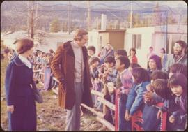 Minister Iona Campagnolo and Hugh Faulkner greet a group of children leaning over wooden fences draped with button blankets, Kispiox, summer 1977