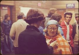 Minister Iona Campagnolo pins a rose to the lapel of an unidentified woman inside a busy hockey arena, summer 1977